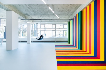 Gathering area with colourful striped wall inspired by the 21 flags of this multicultural office